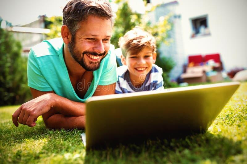 使用膝上型计算机的父亲和儿子在庭院 免版税库存照片
