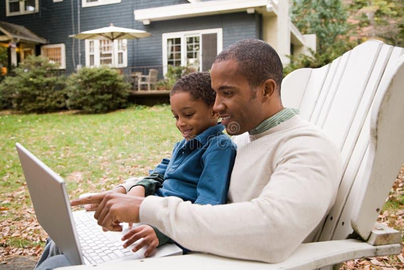 Download 使用膝上型计算机的父亲和儿子在庭院 库存图片. 图片 包括有 父权, 种族, 休闲, 自治权, 了解, 债券 - 62533927