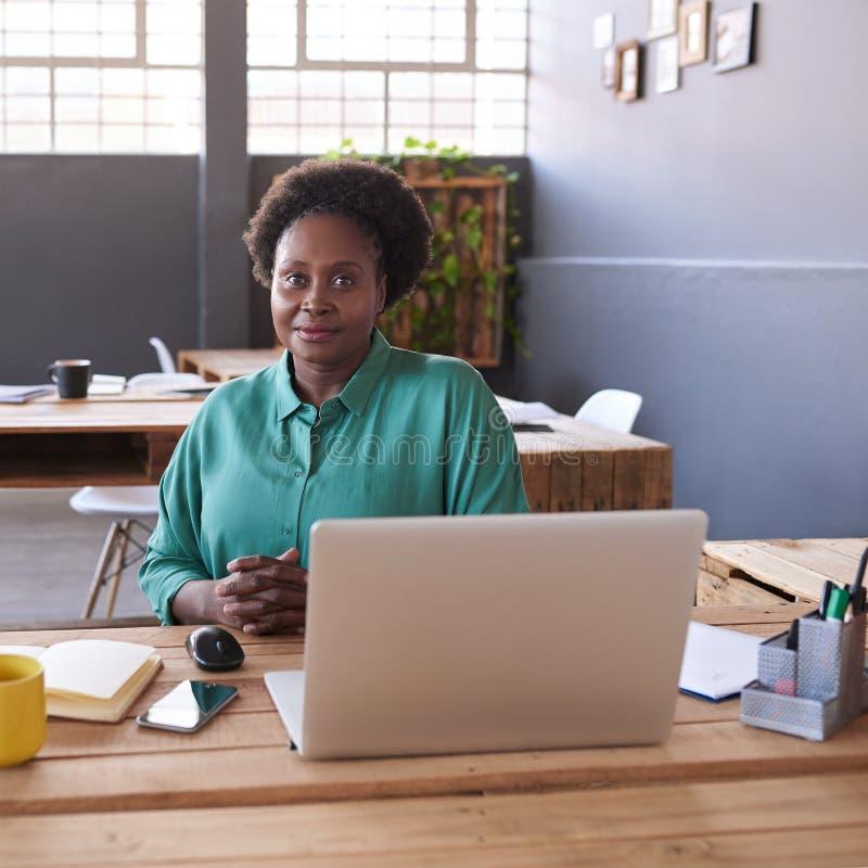 使用膝上型计算机的现代非洲女实业家在一个现代办公室 免版税库存图片