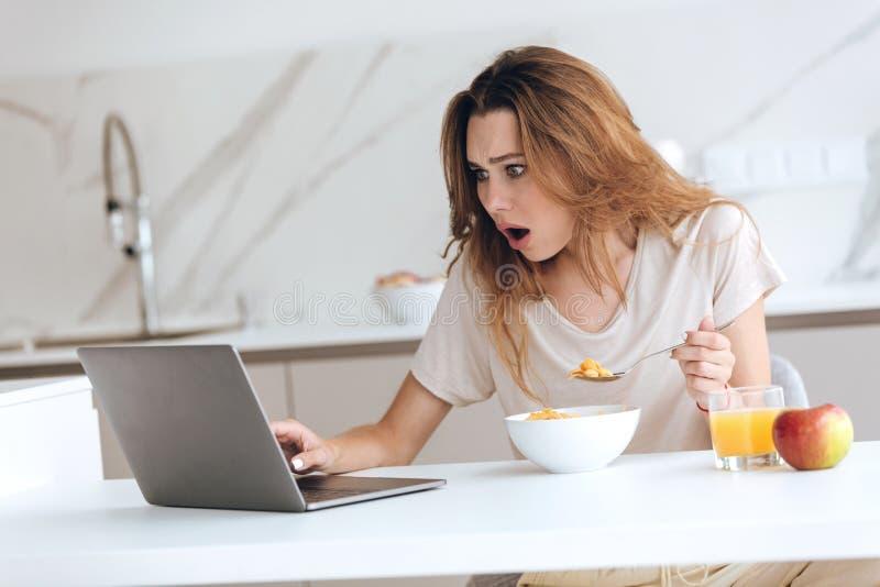 使用膝上型计算机的生气的少妇在厨房 免版税库存照片