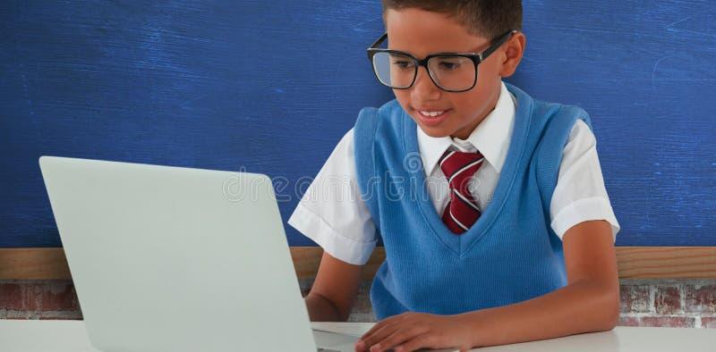使用膝上型计算机的男小学生的综合图象在桌 免版税库存照片