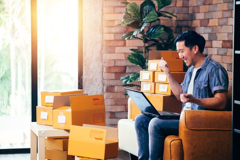 使用膝上型计算机的男性企业家有盒的箱子在家以兴奋 免版税库存照片