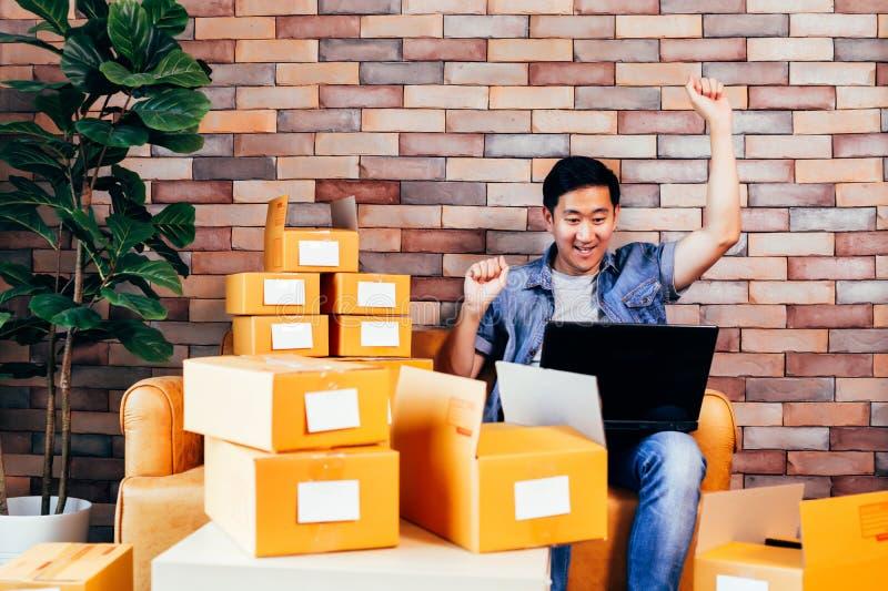使用膝上型计算机的男性企业家有盒的箱子在家以兴奋 库存照片