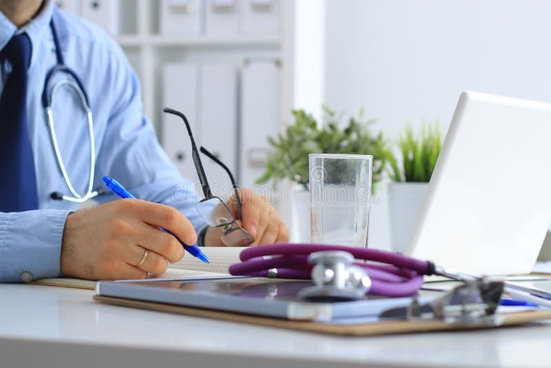 使用膝上型计算机的男性医生,坐与医疗听诊器在他的书桌 免版税库存图片