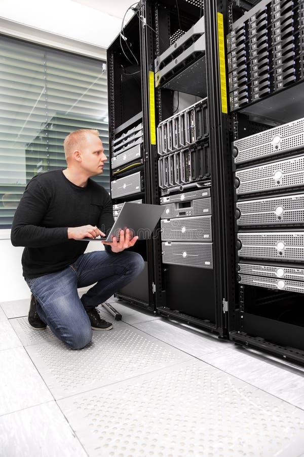 使用膝上型计算机的男性顾问,当监测服务器在Datacen时 免版税库存图片