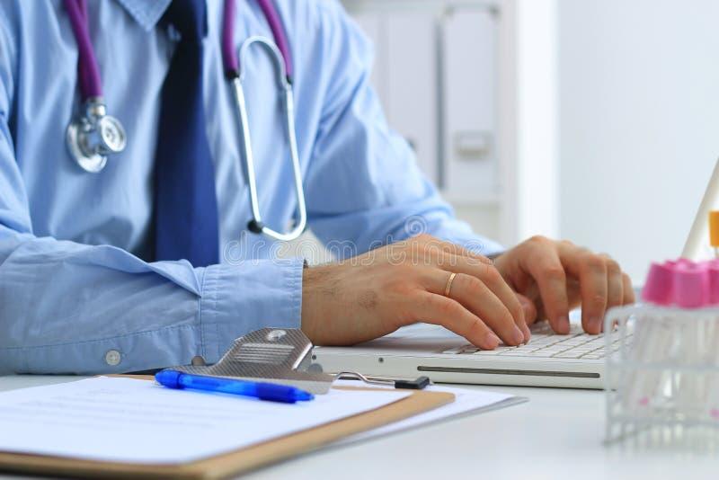 使用膝上型计算机的男性医生,坐在他的书桌 库存图片