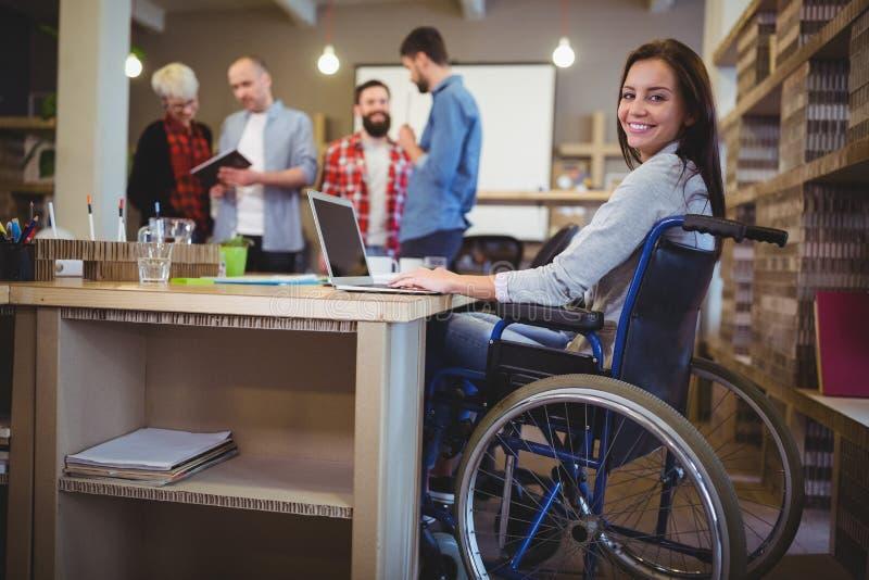 使用膝上型计算机的确信的残疾女实业家在办公室 免版税库存图片
