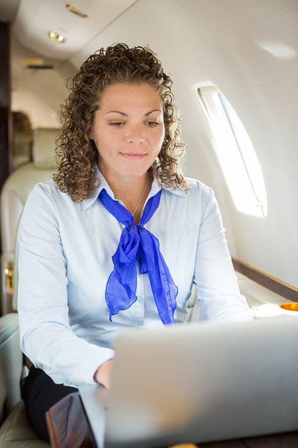 使用膝上型计算机的空中小姐在私人喷气式飞机 库存图片
