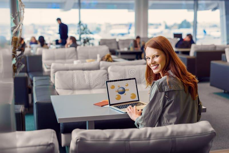 使用膝上型计算机的美丽的女孩在机场 免版税库存图片