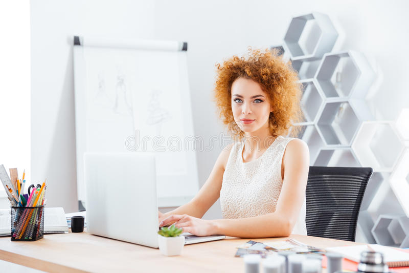 使用膝上型计算机的美丽的确信的妇女时装设计师在办公室 免版税库存照片