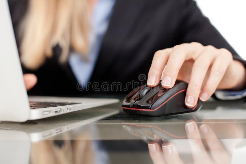 使用膝上型计算机的美丽的年轻女实业家 免版税库存图片