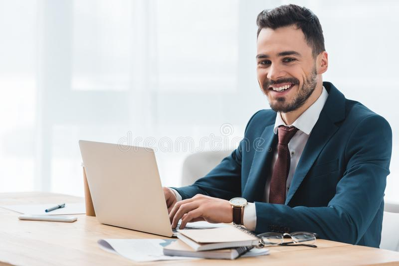 使用膝上型计算机的英俊的年轻商人和微笑对照相机 免版税库存照片