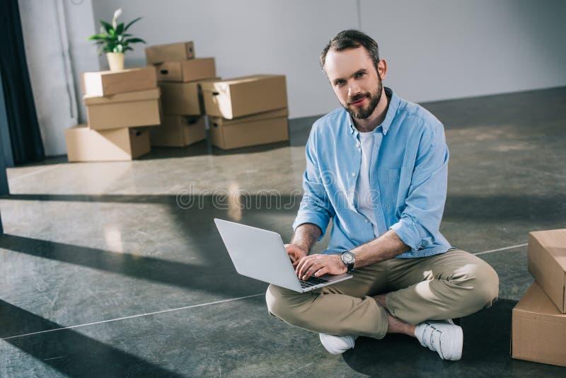 使用膝上型计算机的英俊的有胡子的人和微笑对照相机,当坐地板时 图库摄影