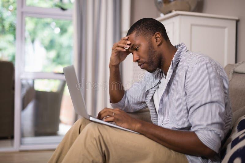 使用膝上型计算机的被拉紧的人,当在家时坐 库存照片