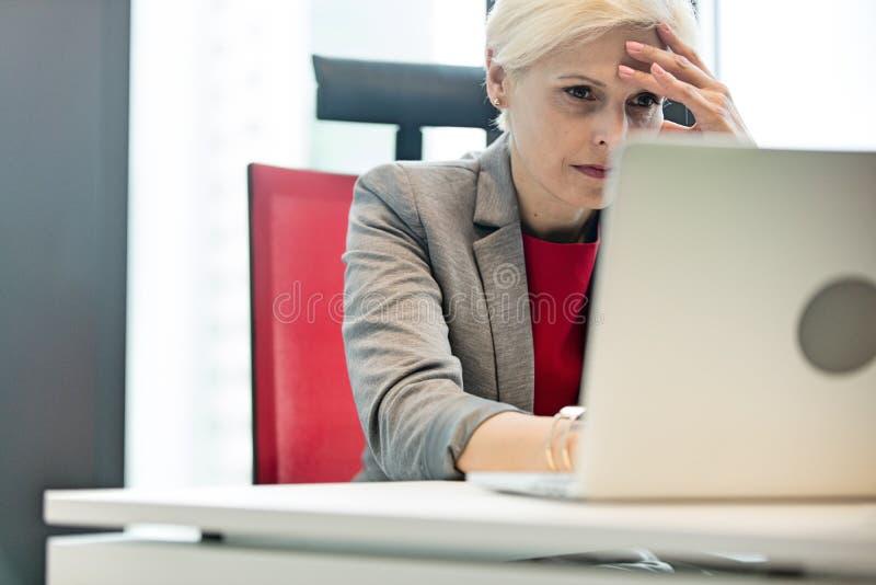 使用膝上型计算机的被拉紧的成熟女实业家在书桌在办公室 免版税图库摄影