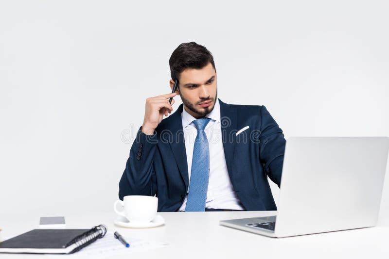 使用膝上型计算机的被聚焦的年轻商人在工作场所 库存图片