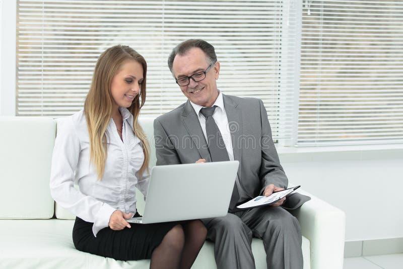 使用膝上型计算机的资深商人和助理坐在办公室的大厅 免版税图库摄影