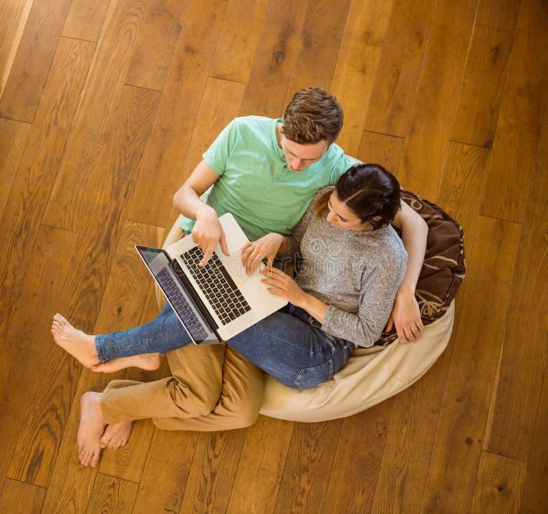 使用膝上型计算机的逗人喜爱的夫妇在装豆子小布袋 库存照片