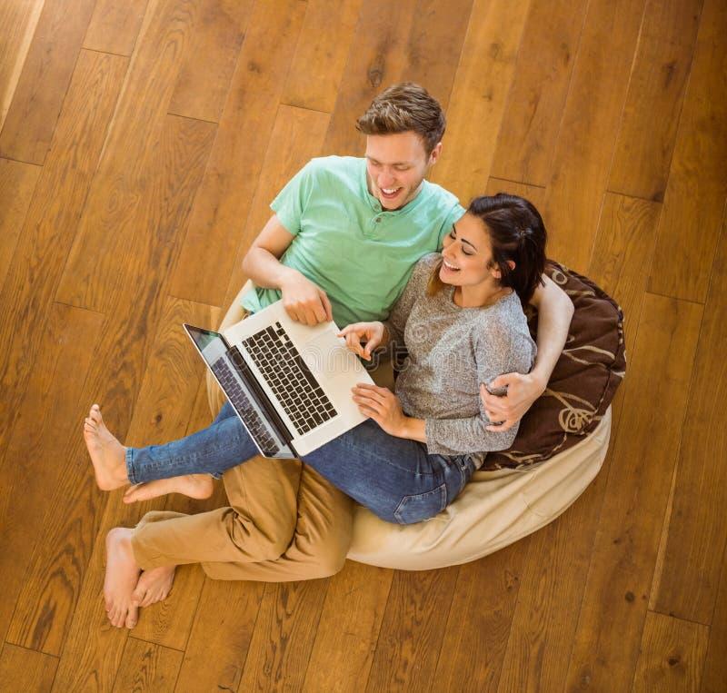 使用膝上型计算机的逗人喜爱的夫妇在装豆子小布袋 免版税库存图片