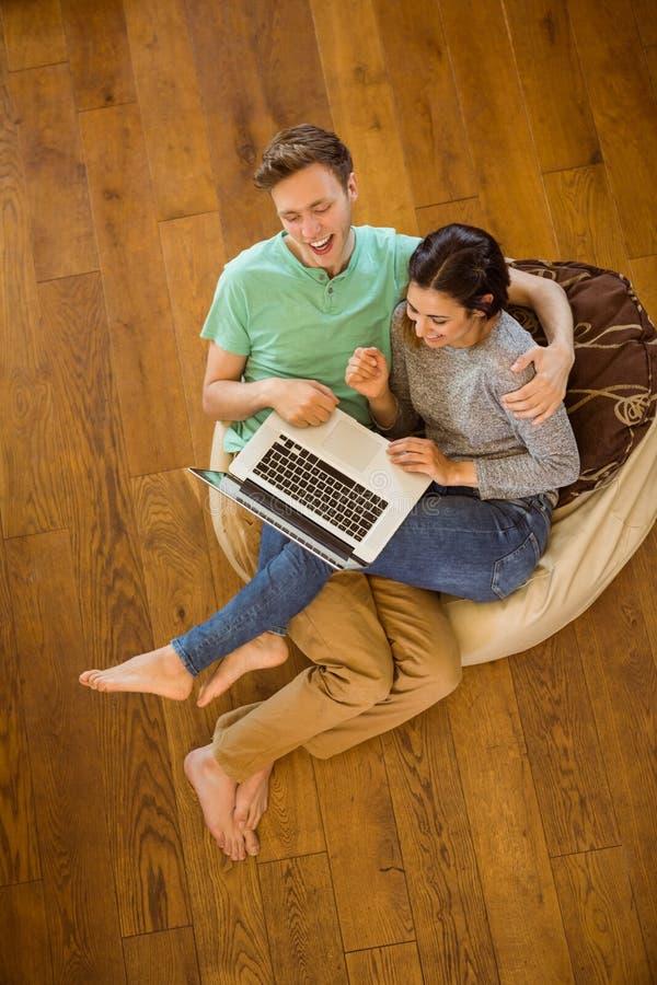 使用膝上型计算机的逗人喜爱的夫妇在装豆子小布袋 免版税图库摄影
