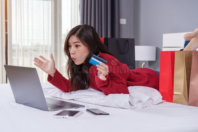 使用膝上型计算机的震惊妇女为与信用卡的网络购物 库存照片