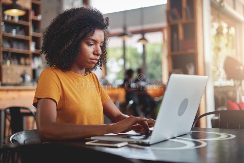 使用膝上型计算机的非洲妇女在咖啡馆 免版税图库摄影