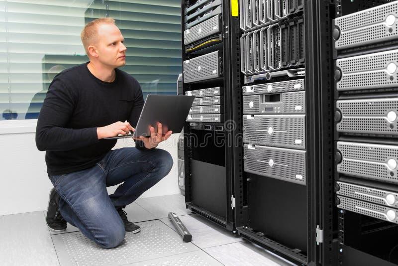 使用膝上型计算机的顾问,当监测服务器在Datacenter时 免版税库存图片