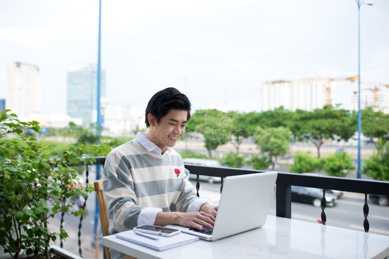 使用膝上型计算机的年轻亚裔学生在城市咖啡馆商店 免版税库存图片