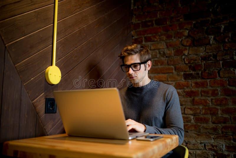 使用膝上型计算机的年轻人在与一杯咖啡的咖啡店 免版税库存照片