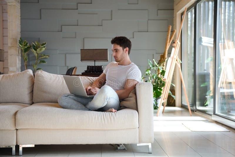 使用膝上型计算机的年轻人,当坐在客厅时 免版税图库摄影