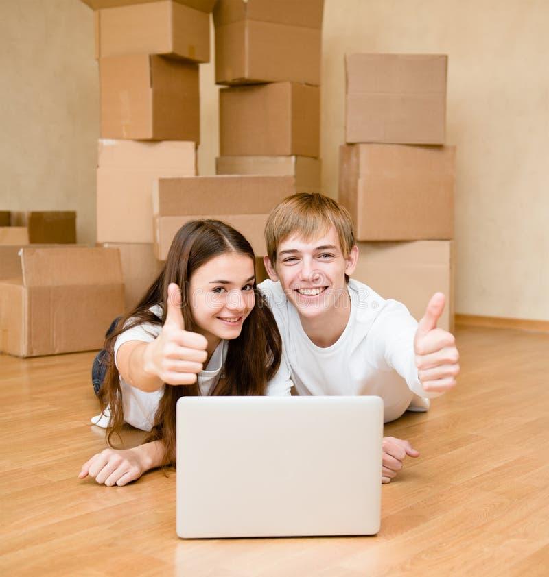 使用膝上型计算机的年轻夫妇在他们新的家庭和显示的赞许 库存照片