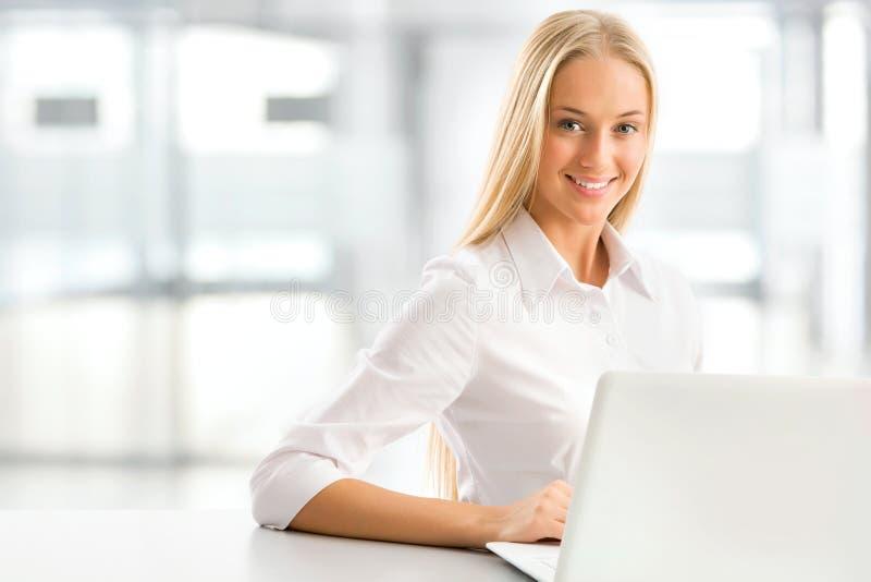 使用膝上型计算机的年轻女商人在办公室 免版税库存图片