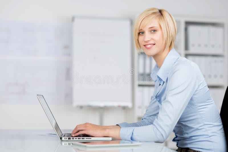 使用膝上型计算机的年轻女实业家在办公桌 免版税库存图片