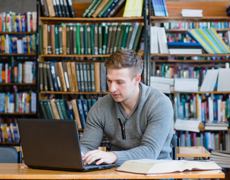 使用膝上型计算机的年轻男学生在大学图书馆 免版税库存照片