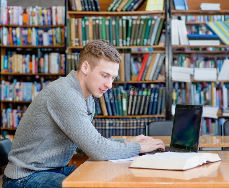 使用膝上型计算机的年轻男学生在大学图书馆 库存照片