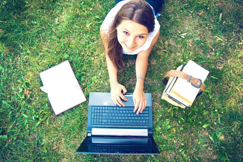 使用膝上型计算机的年轻美丽的大学生女孩 图库摄影