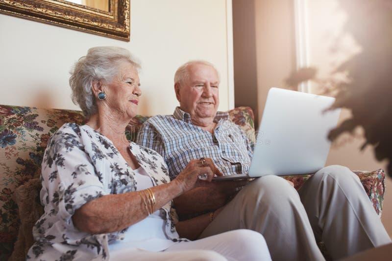 使用膝上型计算机的年长夫妇在家 免版税库存照片