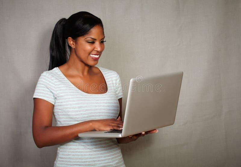 使用膝上型计算机的年轻非洲女孩,当微笑时 免版税库存照片
