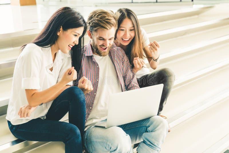使用膝上型计算机笔记本计算机,不同种族的小组大学生或年轻偶然自由职业者的队一起庆祝 免版税库存图片