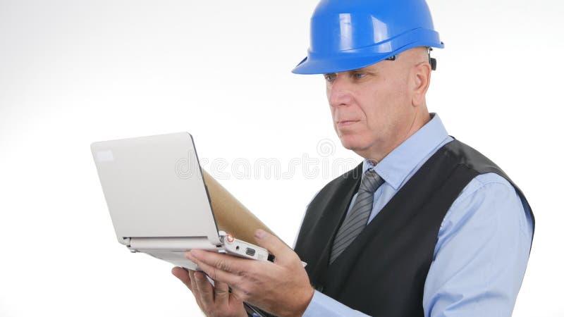 使用膝上型计算机网上通信的严肃的工程师图象 库存照片