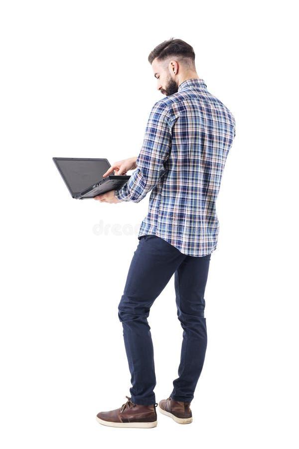 使用膝上型计算机触摸屏的后部观点的现代时髦的有胡子的商人 库存照片