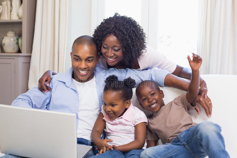 使用膝上型计算机,在长沙发的愉快的家庭一起 免版税库存照片