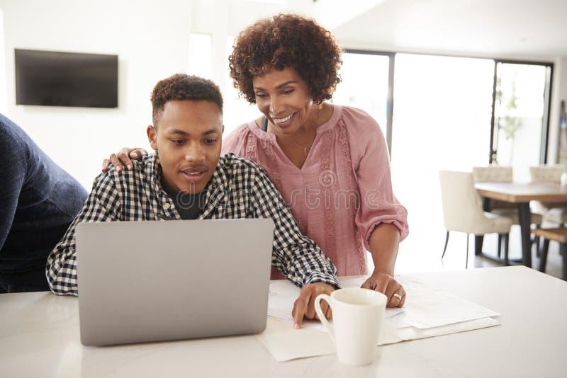 使用膝上型计算机,帮助她的十几岁的儿子的中间年迈的非裔美国人的妈咪做他的家庭作业,关闭  免版税库存图片