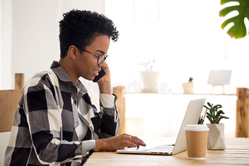 使用膝上型计算机,玻璃的黑人女孩在智能手机谈话 库存图片