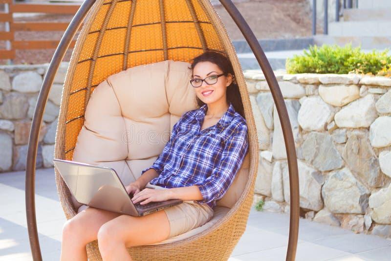 使用膝上型计算机outdoo的美丽的微笑的行家女服玻璃 库存照片
