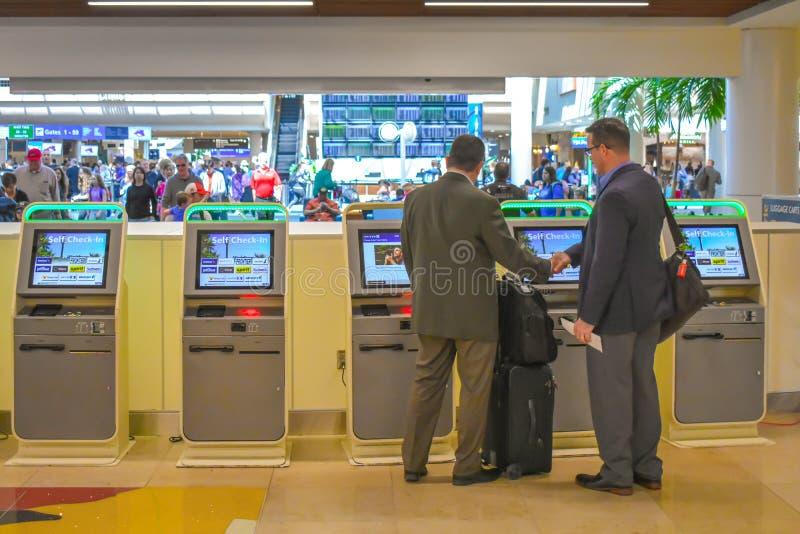 使用自已服务报到的商人在奥兰多国际机场2 免版税图库摄影