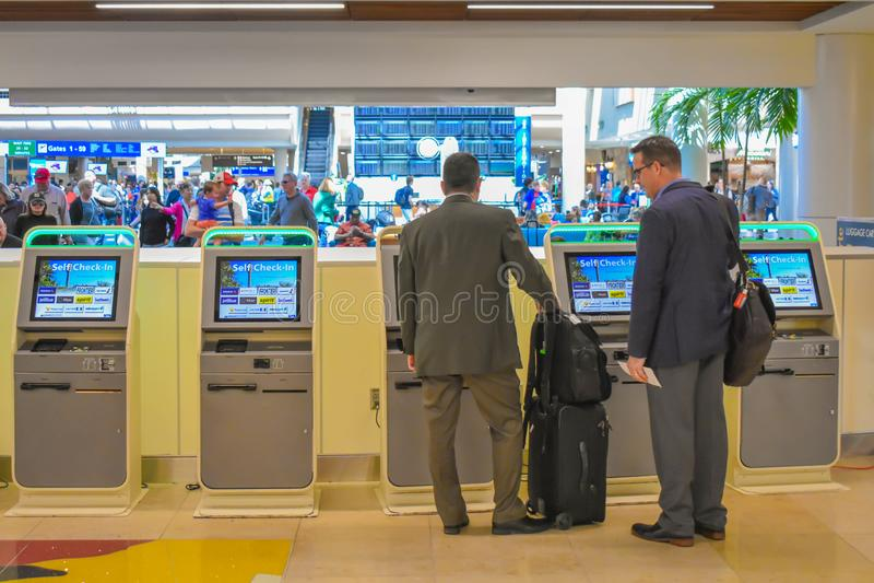 使用自已服务报到的商人在奥兰多国际机场1 免版税库存图片
