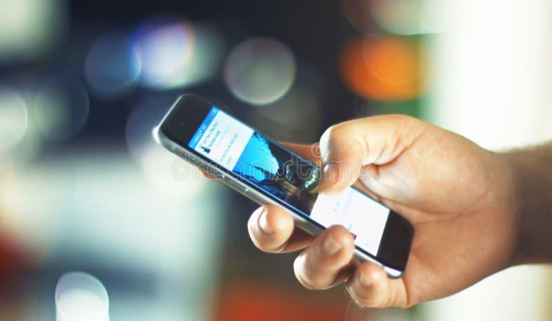 使用苹果计算机iPhone 6s的商人在办公室 免版税图库摄影