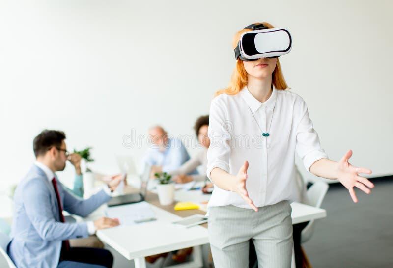使用虚拟现实模拟器的少妇在办公室 免版税库存照片