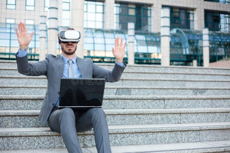 使用虚拟现实模拟器的英俊的年轻商人和做手势,运作在办公楼前面 免版税库存图片
